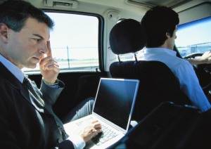 Businessman using laptop in taxi