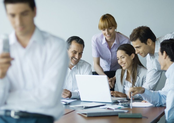 Business Colleagues Gathered Around Laptop, Smiling