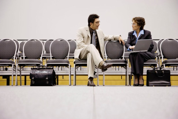 Businessman and Businesswoman Talking in Auditorium