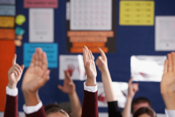High School Students With Raised Hands in Class