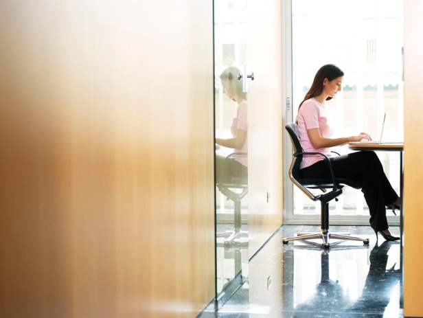 Young businesswoman sitting in office using laptop