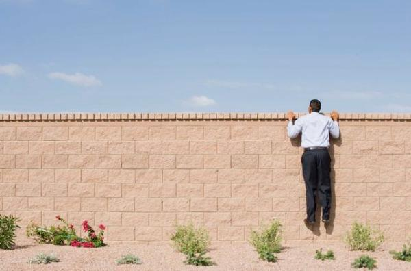 Businessman Looking Over Wall